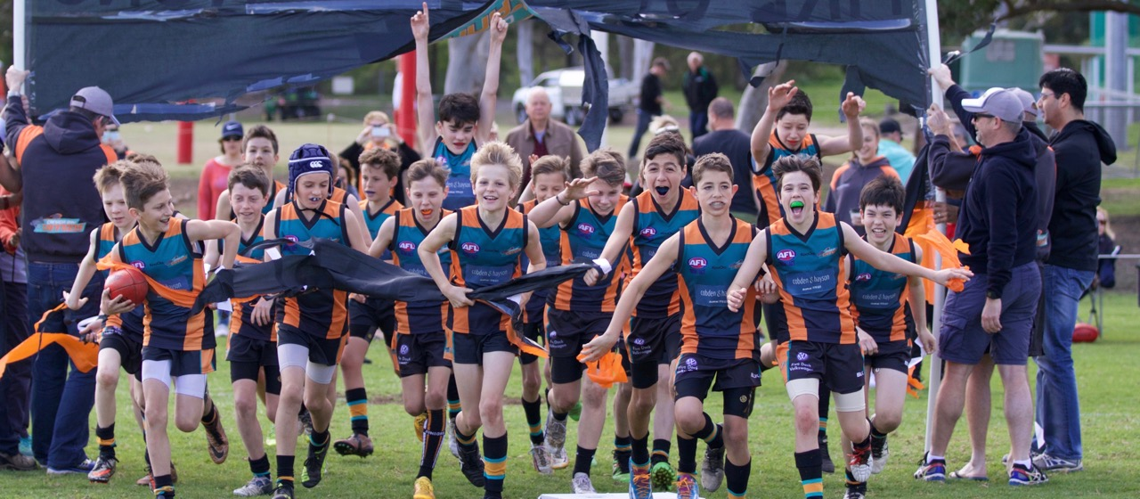 Cannons U12 Div 2 run through grand final banner in 2016